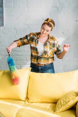 beautiful woman dusting yellow sofa at home