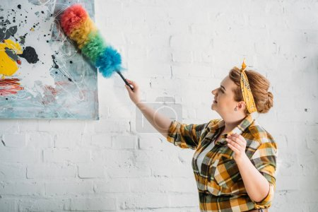 beautiful woman dusting paint on wall at home