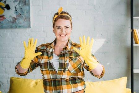 Foto de Hermosa mujer mostrando las manos en guantes de goma para la limpieza en casa - Imagen libre de derechos