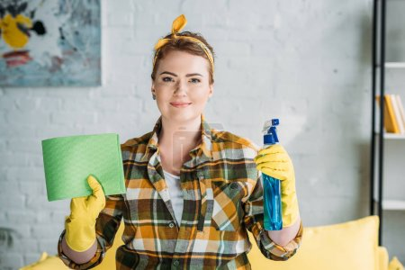 beautiful woman holding rag and spray bottle for cleaning at home