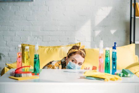 Photo for Beautiful woman looking out from table with cleaning supplies at home - Royalty Free Image
