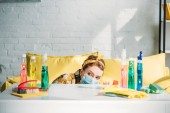 beautiful woman looking out from table with cleaning supplies at home