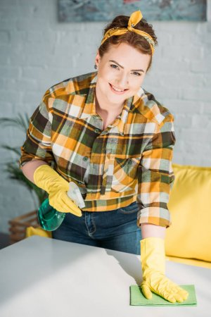 beautiful woman cleaning table with spray bottle and rag at home