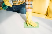cropped image of woman cleaning table with spray bottle and rag at home