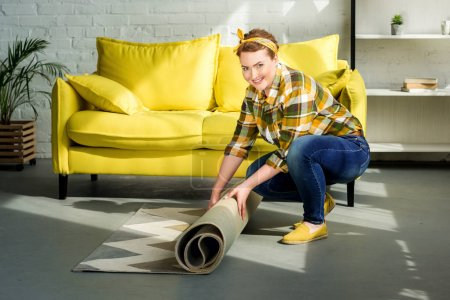 beautiful woman moving away carpet for cleaning floor at home