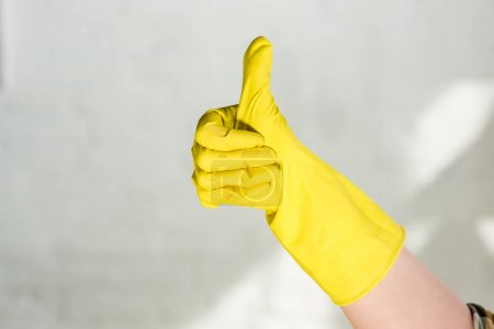 Photo for Cropped image of woman in rubber glove showing thumb up while cleaning at home - Royalty Free Image
