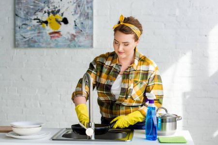 attractive woman washing frying pan in kitchen