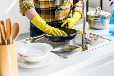 Photo pour Cropped image de femme lavage de poêle dans cuisine - image libre de droit