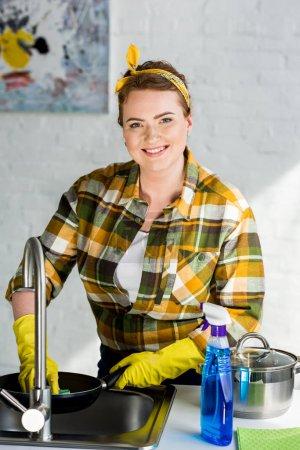 Photo pour Belle souriante femme lavage poêle à cuisine - image libre de droit