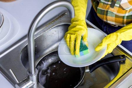 Photo pour Image recadrée de femme plaque à laver avec une éponge de cuisine de lavage - image libre de droit