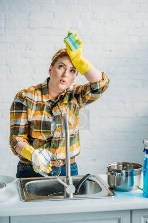 Photo pour Belle femme fatiguée, laver la vaisselle à la cuisine - image libre de droit