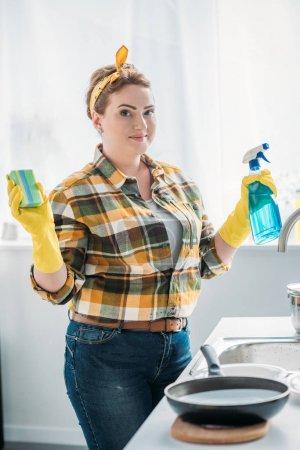 Photo pour Belle femme tenant lavage éponge et jet de bouteille lors du nettoyage à la cuisine - image libre de droit