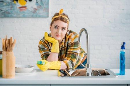 Photo pour Belle femme se penchant sur le comptoir de cuisine et la tenue lavage éponge - image libre de droit