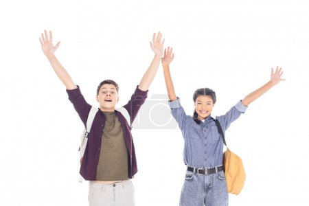 portrait of excited teenagers with backpacks outstretching arms isolated on white