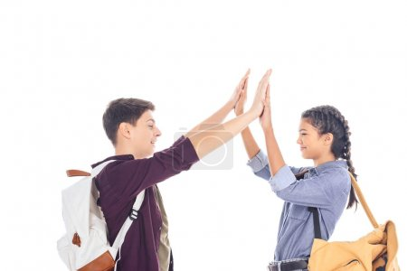 side view of teenagers with backpacks giving high five to each other isolated on white