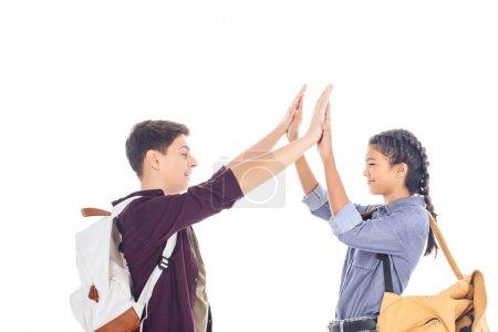 Foto de Vista lateral de los adolescentes con mochilas dando alta cinco mutuamente aislados en blanco - Imagen libre de derechos