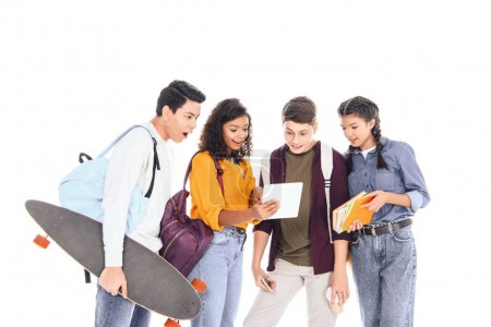 shocked multiracial students with backpacks and longboard using tablet together isolated on white