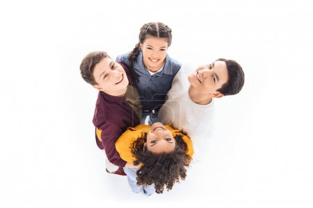 overhead view of smiling multicultural teenagers hugging each other isolated on white