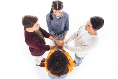 overhead view of multicultural teen friends holding hands together isolated on white