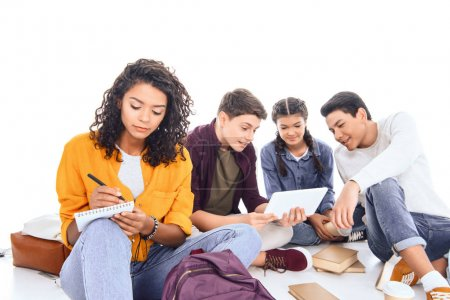 multiracial students with backpacks and notebooks isolated on white