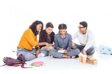 interracial students doing homework together isolated on white