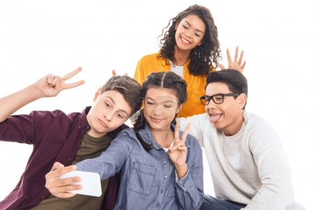 portrait of multicultural students taking selfie on smartphone together isolated on white