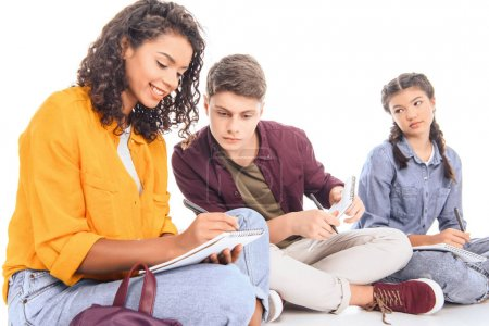 multiethnic students doing homework together isolated on white