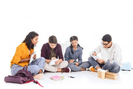 multiracial students doing homework together isolated on white
