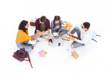 high angle view of multiracial students doing homework together isolated on white