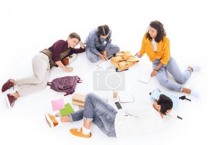 Foto de Alto ángulo visión de interraciales estudiantes con cuadernos y mochilas descanso aislado en blanco - Imagen libre de derechos