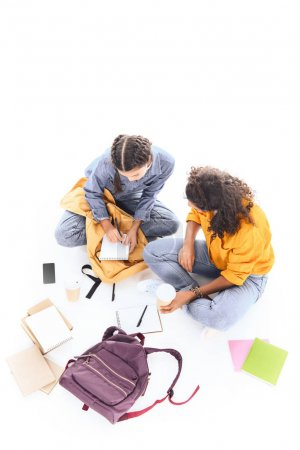 overhead view of multiethnic students doing homework together isolated on white