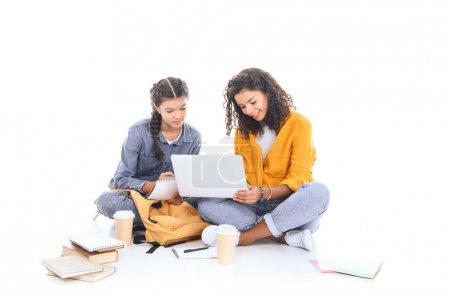 multicultural teenagers using laptop together isolated on white