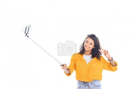 portrait of smiling african american teenager taking selfie on smartphone isolated on white