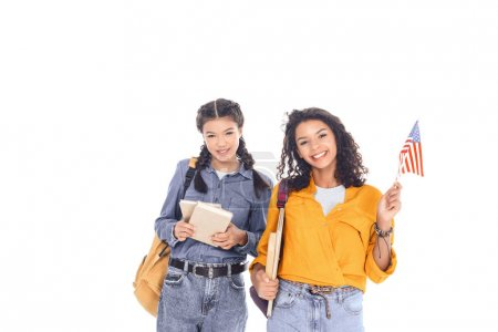 portrait of smiling interracial students with backpacks, books and american flag isolated on white