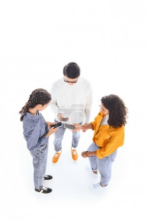 high angle view of interracial teenagers using smartphones isolated on white