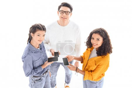 Foto de Vista de ángulo alto de sonrientes adolescentes interraciales con smartphones aislados en blanco - Imagen libre de derechos