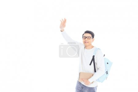 portrait of asian student with backpack and notebooks waving to someone isolated on white