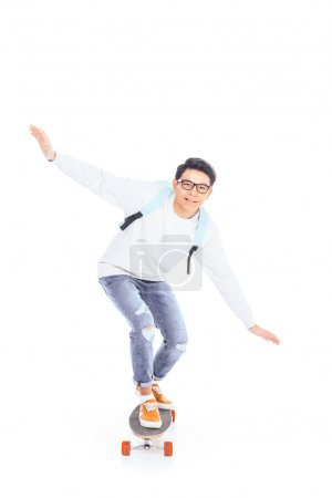asian teenager with backpack riding skateboard isolated on white