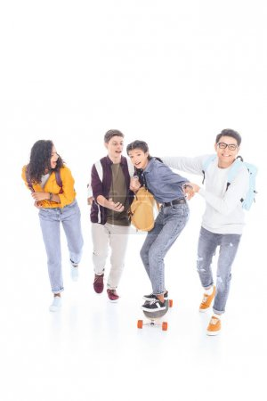 multiracial teenagers with backpacks and skateboard isolated on white