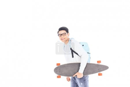 side view of asian teenager with backpack and skateboard isolated on white