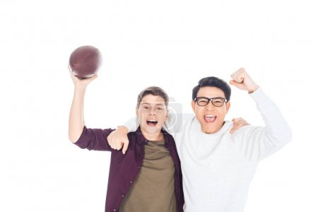 portrait of cheerful interracial teen boys with rugby ball isolated on white