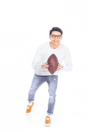 smiling asian teenager in eyeglasses with rugby ball in hands isolated on white