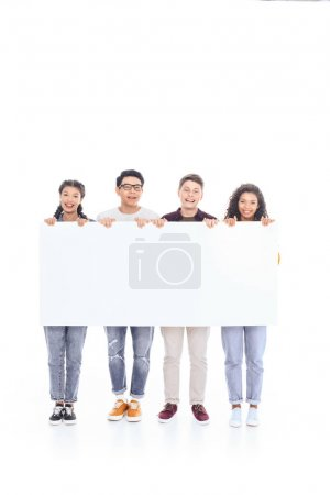 smiling multiracial teenagers holding blank banner together isolated on white