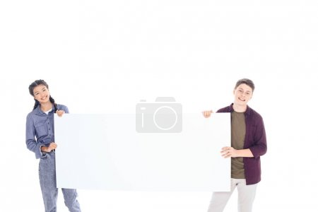portrait of smiling teenagers holding empty banner isolated on white