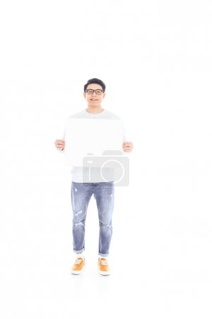 smiling asian teenager with empty banner in hands isolated on white
