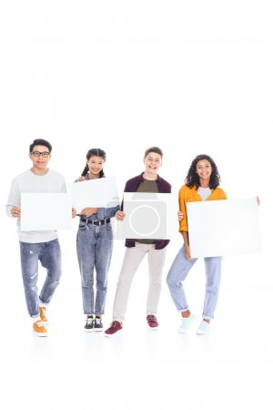 smiling interracial teenagers holding blank banners in hands isolated on white