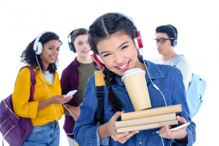 teen student girl in headphones with coffee to go isolated on white with her friends chatting on background