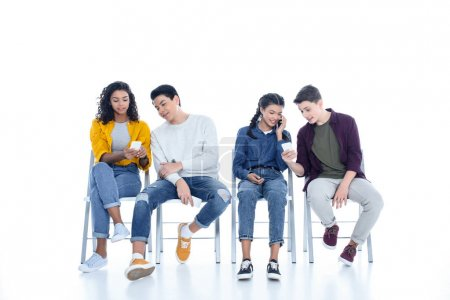 group of teen students using smartphones on chairs isolated on white