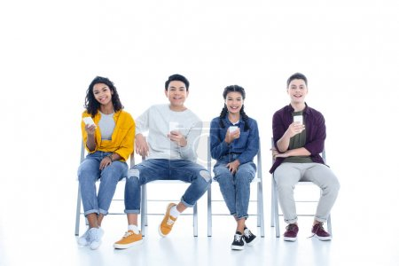 multiethnic teen students with smartphones sitting on chairs isolated on white