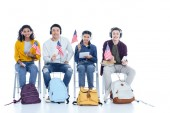 group of teen students in headphones with usa flags sitting on chairs isolated on white